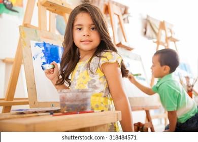 Portrait of a gorgeous little Hispanic girl holding a paintbrush and working on a painting for art class