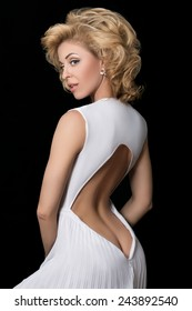 Portrait of gorgeous mature blond woman in white dress standing back to camera over black background