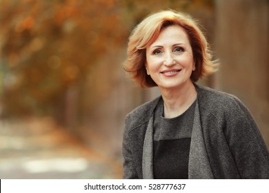 Portrait of gorgeous middle aged woman in autumn park