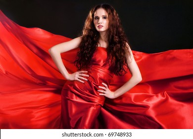 Portrait of gorgeous model in red clothing against black background
