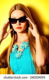 Portrait of a gorgeous pin-up woman over yellow background. Beauty, fashion concept. Optics. Jewelry.