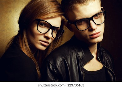 Portrait of gorgeous red-haired fashion twins in black clothes wearing trendy glasses and posing over golden background together. Studio shot.