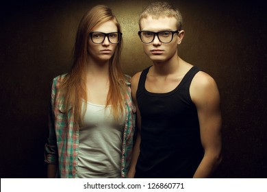 Portrait of gorgeous red-haired fashion twins in casual shirts wearing trendy glasses and posing over golden background together. Studio shot.