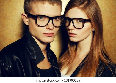 Portrait of gorgeous red-haired fashion twins in black clothes wearing trendy glasses and posing over golden background together. Perfect hair. Natural make-up. Perfect skin. Close up. Studio shot.