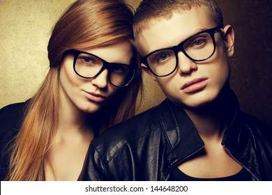Portrait of gorgeous red-haired fashion twins in black clothes wearing trendy glasses and posing over golden background together. Perfect hair & skin. Hipster style. Close up. Studio shot