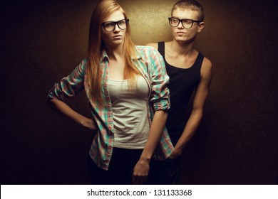 Portrait of gorgeous red-haired (ginger) fashion twins in casual shirts wearing trendy glasses and posing over golden background together. Boy winking to his sister. Studio shot.