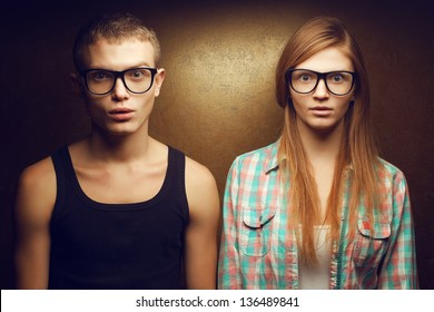 Portrait of gorgeous red-haired (ginger) fashion twins in casual shirts wearing trendy glasses and posing over golden background together with wow (scared) faces. Hipster style. Studio shot.