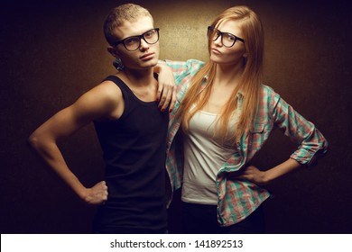 Portrait of gorgeous red-haired (ginger) fashion twins in casual shirts wearing trendy glasses and posing over golden background together. Studio shot