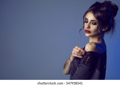 Portrait of gorgeous sexy dark-haired tattooed young woman with provocative make-up and updo hair taking a black silk peignoir off her shoulder seductively. Copy-space. Close up