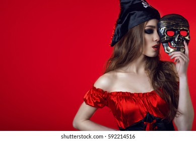 Portrait of gorgeous sexy woman with closed eyes and provocative make-up in pirate costume hiding the half of her face behind skull mask. Isolated on bright red background. Close up. Copy-space