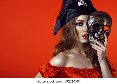 Portrait of gorgeous sexy woman with provocative make-up in pirate costume hiding the half of her face behind skull mask. Isolated on bright red background. Close up. Copy-space