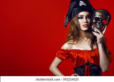 Portrait of gorgeous sexy woman with provocative make-up in pirate costume holding skull mask next to her face. Gamble and casino concept. Isolated on bright red background. Close up. Copy-space