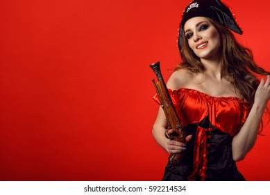 Portrait of gorgeous sexy woman with provocative make-up biting her lip and holding vintage wooden gun. Gamble and casino concept. Isolated on bright red background. Close up. Copy-space