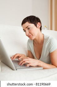Portrait of a gorgeous short-haired woman using a laptop in her living room
