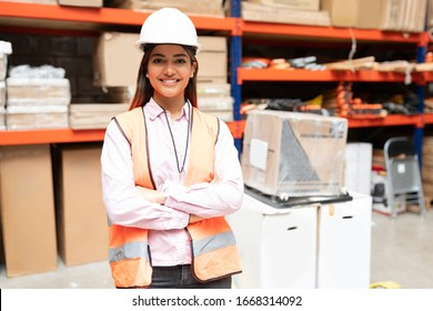 Portrait of gorgeous smiling employee standing with arms crossed against rack at warehouse