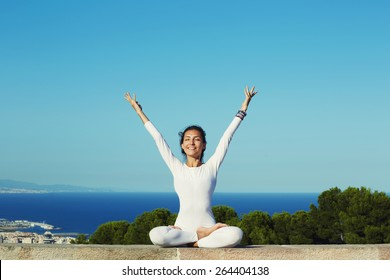 Portrait of gorgeous smiling woman practicing yoga by raising her hands feeling so good and happy, young woman seeking enlightenment through meditation, relaxed girl performing yoga routine, filter