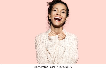 Portrait of gorgeous smiling woman wearing snow white knitted sweater. Cute girl looking at camera with happiness. Happy model posing in studio. Isolated on pink background