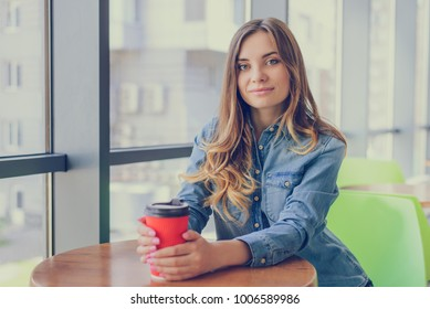 Portrait of gorgeous smiling young beautiful excited cheerful with curly hair hairstyle woman drinking takeaway coffee from disposable cup. She is having a break at work.