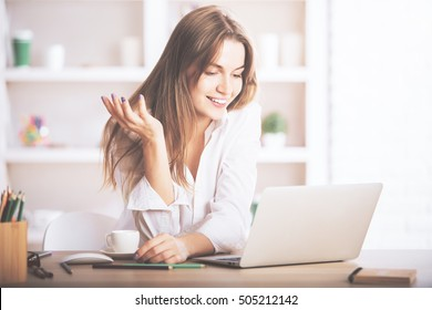 Portrait of gorgeous, smiling young female using laptop computer at workplace