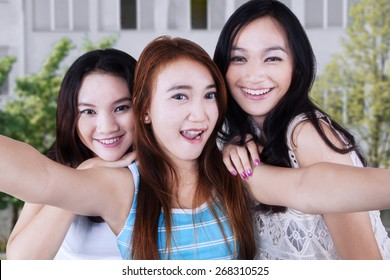 Portrait of gorgeous teenage girls smiling at the camera while taking a self picture together
