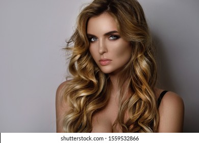 Portrait of gorgeous woman with a beautiful curly hair and professional makeup