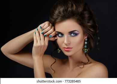Portrait of gorgeous woman with a beautiful make-up and shiny earrings in studio