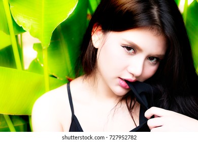 Portrait gorgeous woman: A charming woman is biting her shirt. Attractive girl looks so sexy and bitchy or naughty.  A beautiful girl looks so refreshed and playful with beautiful natural background.