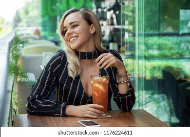 Portrait gorgeous woman holding phone in hand while sitting on the cafe terrace with a fresh drink with ice and orange slices, posing with a shiny white smile.