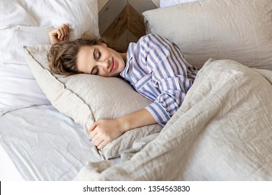Portrait of gorgeous woman wearing striped pajamas in cozy bedroom. Calm female immersed in pleasant recreation and daydreaming. Girl in serene slumber