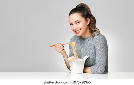 Portrait of a gorgeous young brunette eating asian food with chopsticks.