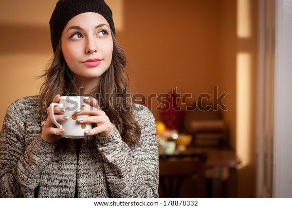 Portrait of a gorgeous young brunette relaxing with cup of hot beverage.