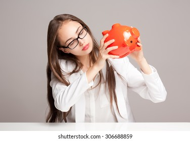 Portrait of a gorgeous young brunette woman holding piggy bank.
