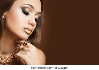 Portrait of a gorgeous young brunette woman wearing gold luxury jewelry.