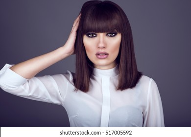 Portrait of gorgeous young dark-haired woman with provocative make up and expressive eyes looking straight and touching hair with her hand. Close up. Studio shot.