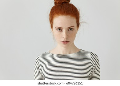 Portrait of gorgeous young female with clean healthy skin with freckles and hair knot staring at camera, having serious confident look, dressed in casual striped top. People and lifestyle concept
