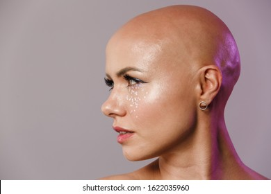 Portrait of gorgeous young half-naked bald woman with glitter face posing at camera isolated over gray background