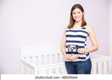 Portrait of a gorgeous young Hispanic pregnant woman holding a picture of her ultrasound in front of her belly