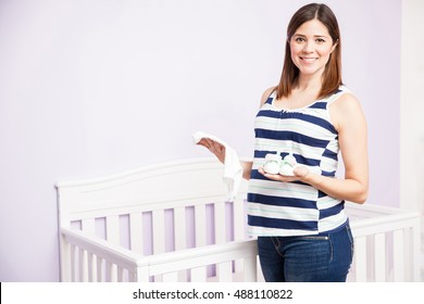 Portrait of a gorgeous young Hispanic pregnant woman holding some baby clothes next to a crib in a nursery