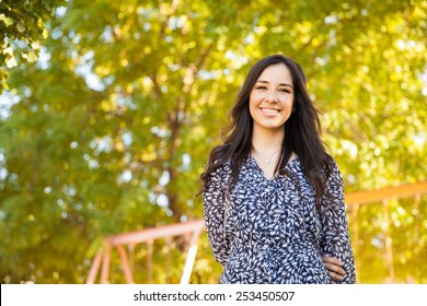 Portrait of a gorgeous young Hispanic woman hanging out at a park and smiling