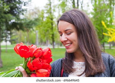 Portrait of a gorgeous young lady holding red tulip bouquet outdoor in the park on springtime