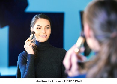 Portrait of gorgeous young woman applying her makeup while sitting at mirror in the photostudio.