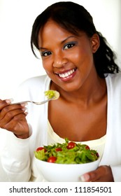 Portrait of a gorgeous young woman eating vegetable salad on a bowl and looking at you.