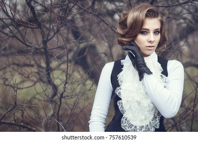 Portrait of gorgeous young woman with elegant Victorian hairstyle and beautiful make up wearing old-fashioned gown with jabot standing at the dry tree holding her hand in leather glove at her cheek
