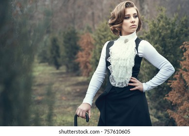 Portrait of gorgeous young woman with elegant Victorian hairstyle wearing old-fashioned gown with jabot leaning on her cane and looking aside, misty autumn park on background. Vintage style