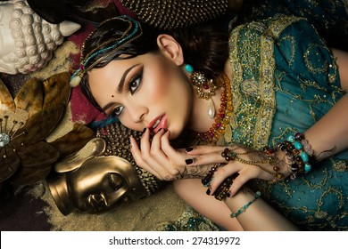 Portrait of gorgeous young woman lying in sand with buddha heads