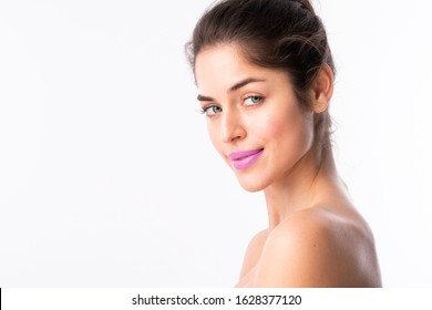Portrait of gorgeous young woman with perfect skin wearing purple lipstick while posing at isolated white background with copy space.