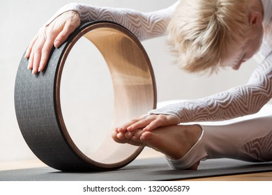 Portrait of gorgeous young woman practicing yoga indoor with a help of yoga wheel.