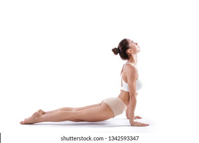 Portrait of gorgeous young woman practicing yoga. Beautiful girl practice cobra asana isolated on white. Calmness and relax.
