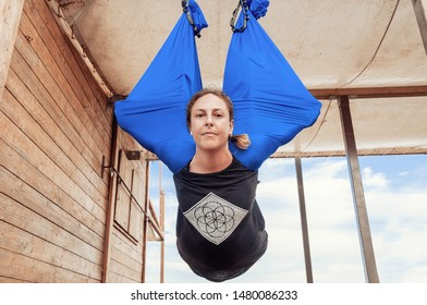 Portrait of gorgeous young woman practicing fly-yoga outdoor,  Antigravity yoga outdoors by the sea .  Healthy and Yoga Concept.