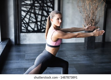 Portrait of gorgeous young woman practicing yoga indoor, Warrior of Light asana.